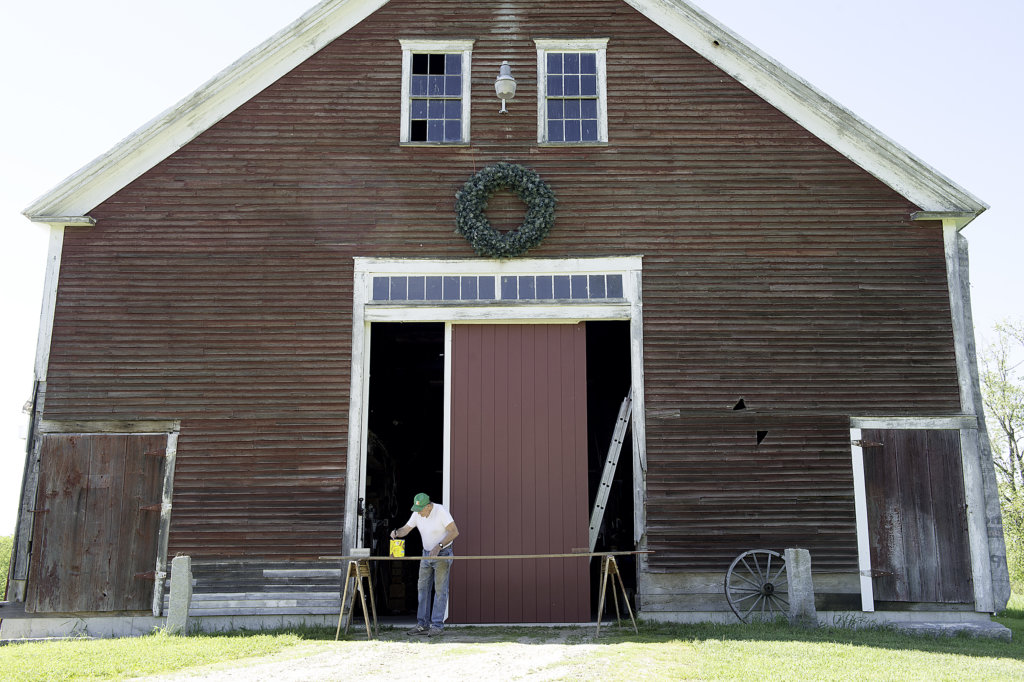 Don Rose stains boards for the new barn door he is building on his hay farm in Greene on Thursday. Rose had the barn moved four years ago and once it was ... & New door for an old barn - Lewiston Sun Journal