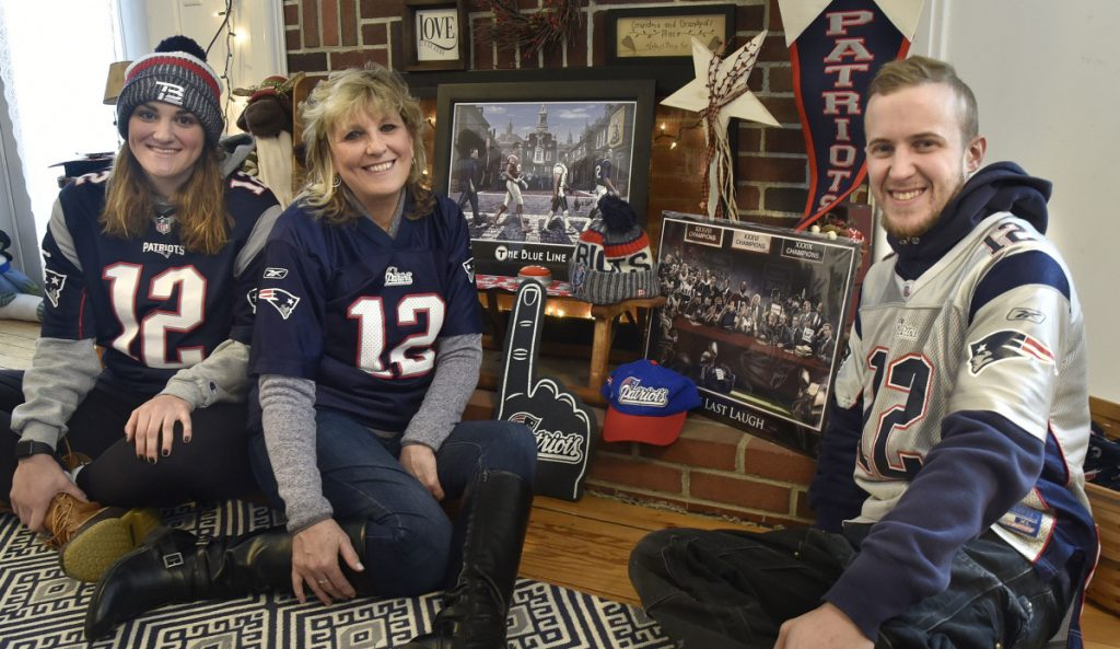 Members of the Mark and Deb Tanner family, hardcore fans of the New England Patriots, gather around a team memorabilia display at their home in Skowhegan on Monday. Deb Tanner, center, is flanked by children Kaley and Josh. Her husband, the Rev. Mark Tanner, is out of state this week, but picked the correct score of the AFC championship game against the Kansas City Chiefs.
