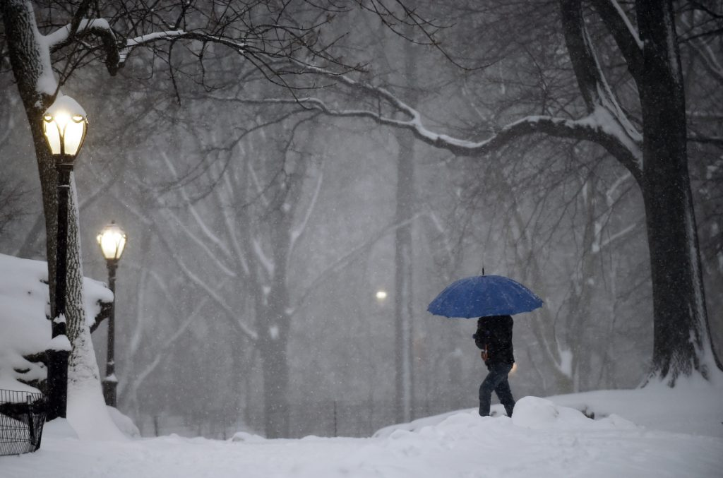 A pedestrian walks through New York City's snow-covered Central Park. Forecasters and managers at the National Weather Service are not getting paid during the partial government shutdown.