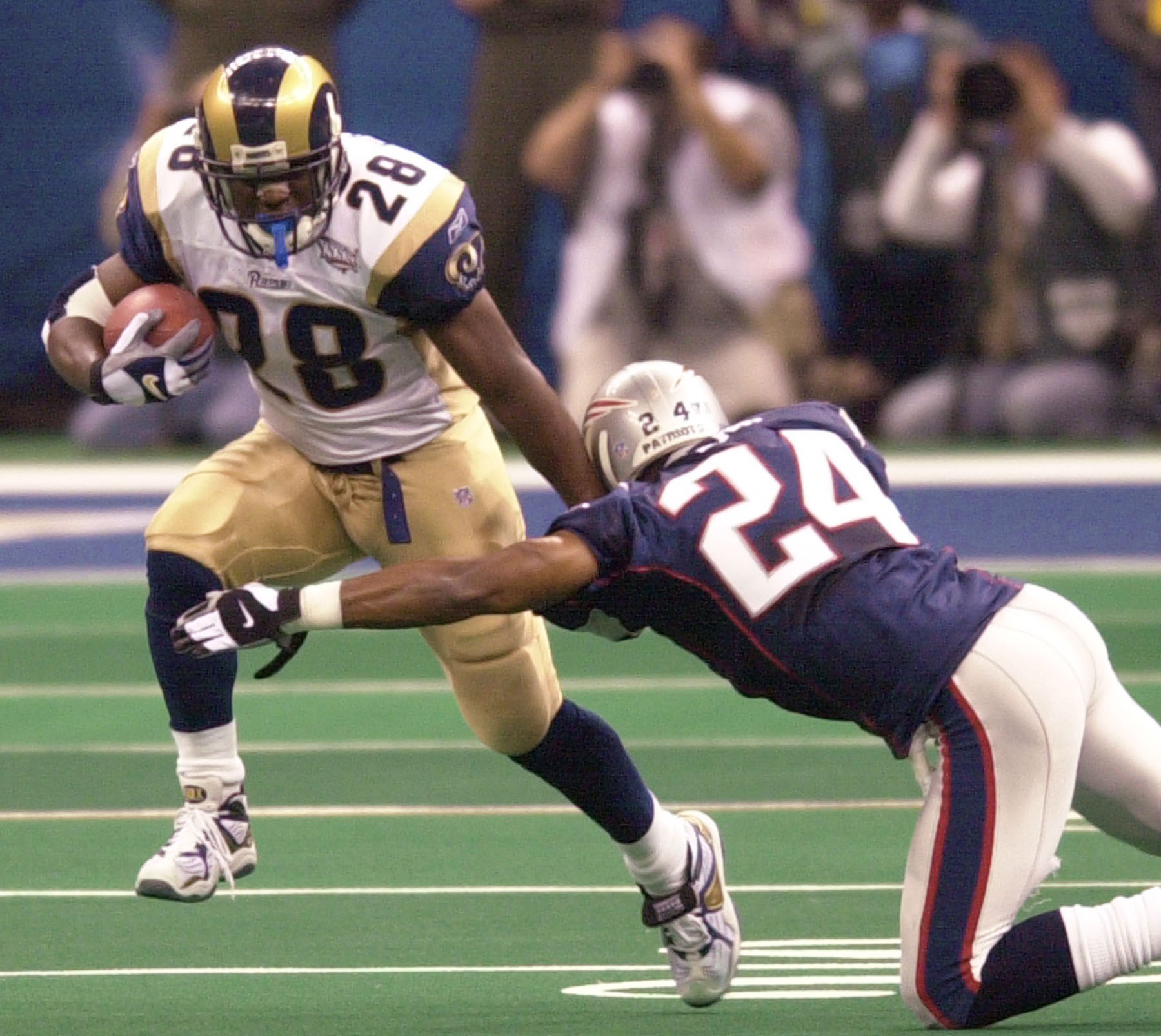 ... St. Louis Rams running back Marshall Faulk (28) fending off New England  Patriots cornerback Ty Law (24) during first-quarter play of Super Bowl  XXXVI in ... eb448bf9a
