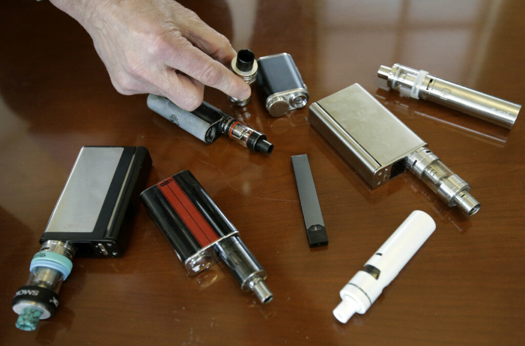 Marshfield (Mass.) High School Principal Robert Keuther displays vaping devices that were confiscated from students in places such as restrooms or hallways at the school. Associated Press/Steven Senne
