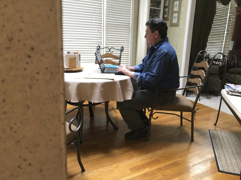 In this Friday, Feb. 15, 2019, photo Kevin McCreanor works on a laptop in Atlanta. The first tax filing season under the new federal tax law is proving to be surprising, confusing (and occasionally frightening) for some Americans. McCreanor and his wife normally get a sizeable refund each year. While they know waiting for a large refund isn't the best strategy financially, they like a refund and they put anything they get back toward their daughters' education. Their income, earned primarily from his wife's job in telecom, can vary greatly, so there was comfort in never facing a big bill.