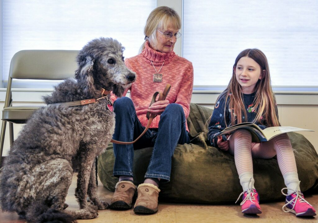 Lily the labradoodle, left, and Gail Balch listen as Sophie Moore reads them a book aloud Thursday at Isaac F. Umberhine Public Library in Richmond.