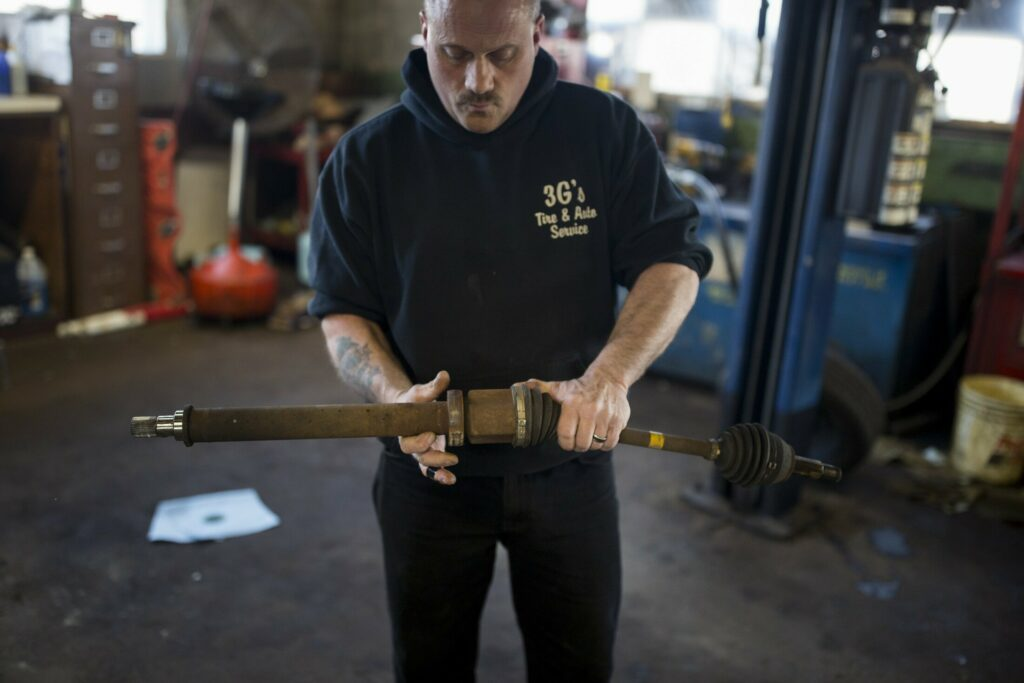 Bob Byrnes at 3G's Tire and Auto in Portland holds an axle he removed Tuesday from a car that was brought in with a damaged bearing after it hit a pothole. The bearing is about a $400 repair. Josh Byrnes, the manager of the shop, said about 15-20 cars per week are brought in because of pothole damage.