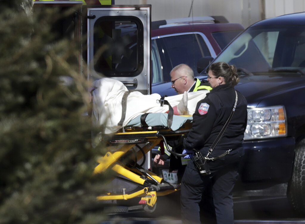 Emergency medical technicians carry a person on a stretcher into an ambulance outside the Quality Inn on Thursday in Manchester, N.H.