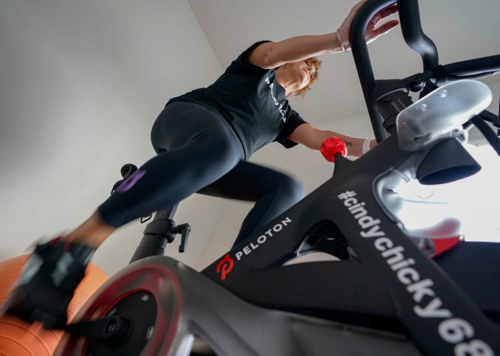 Cindy Cicchinelli uses her Peloton exercise machine in the workout room of her Pittsburgh townhouse. K. Sreekumaran Nair, a Mayo endocrinologist, suggests doing 35 minutes of HIIT three days per week; doing two nonconsecutive days of strength training, focusing on core muscles, arms and legs, with three sets for each muscle group; and taking walks of 7,000 to 10,000 steps on the other two days.