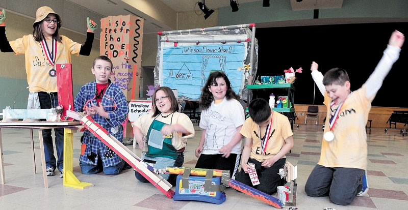 IT WORKS: Members of the Winslow Elementary School Odyssey of the Mind team react with cheers after practicing with their Rube Goldberg invention that replaces the common watering can on Monday. The team is preparing to raise money to compete in the World Finals of the Odyssey of the Mind competition in Maryland.