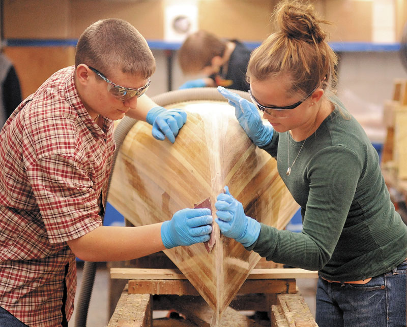 SHIPSHAPE: Ivan Beaulieu, left, and Megan Orchard work on a canoe they built from scratch in the Outdoor Resources class during the skills showcase at the Somerset Career & Technical Center in Skowhegan Wednesday.