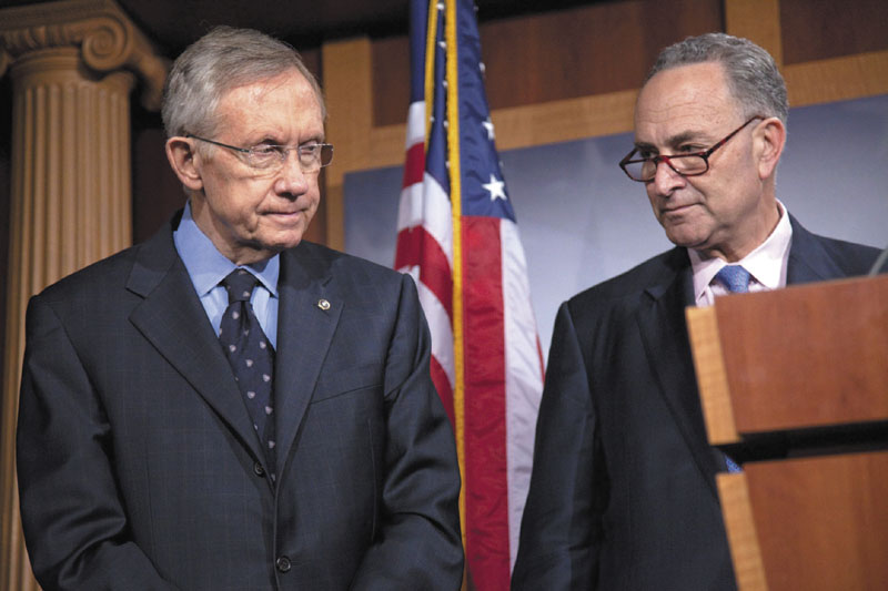NOT LOOKING ENTHUSED: Senate Majority Leader Harry Reid, D-Nev., left, and Sen. Charles Schumer, D-N.Y., pause during a news conference on Capitol Hill in Washington on Thursday. Congress sent President Barack Obama hard-fought legislation cutting a record $38 billion from federal spending on Thursday, but it was a bill no one claimed to like in its entirety.