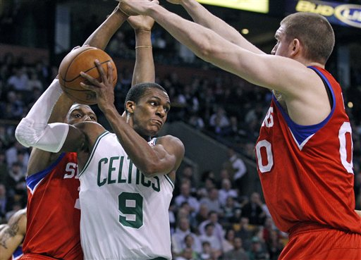 Boston Celtics guard Rajon Rondo (9) looks to pass against the defense of Philadelphia 76ers forward Thaddeus Young, left, and center Spencer Hawes, right, during the Celtics' 99-82 win Tuesday in Boston.