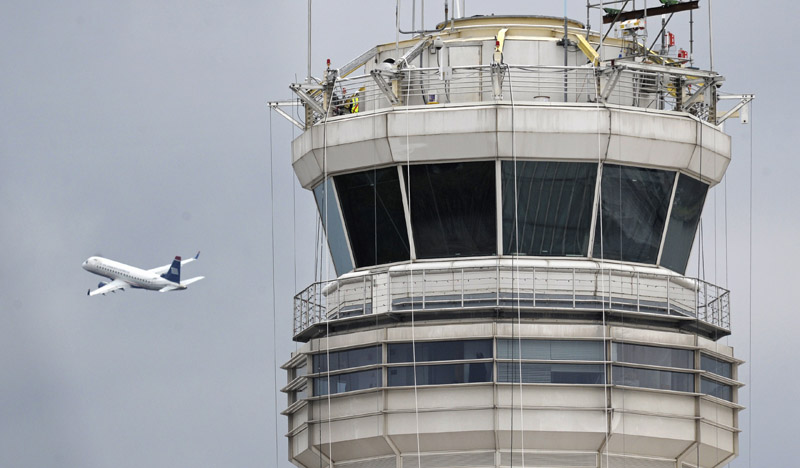 A passenger jet flies past the FAA control tower recently at Washington's Ronald Reagan National Airport, where a control tower supervisor who was unavailable to aid two airliners was suspended in March.