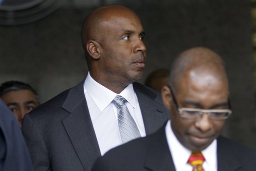 Former baseball player Barry Bonds, left, leaves federal court Tuesday in San Francisco. Prosecutors rested their case against Bonds in his perjury trial Tuesday.