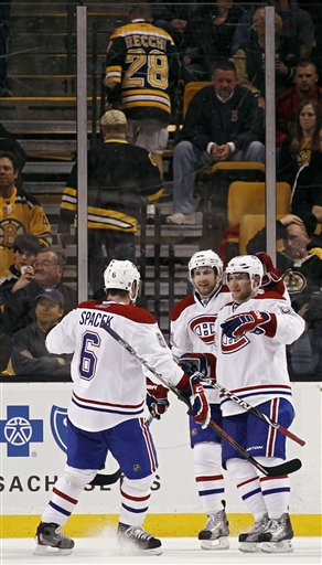 Boston Bruins fans walk up the stairs as Montreal's Yannick Weber, bottom right, is congratulated by teammates Tom Pyatt and Jaroslav Spacek (6) after scoring against the Bruins during the second period of the Canadiens 3-1 win in Game 2 of their first-round playoffs series Saturday in Boston.