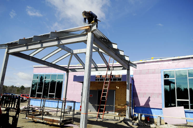 Dan Witham Jr., of Yankee Welding, welds together the entry canopy of the new Chelsea School Thursday. The building is 60 percent complete.