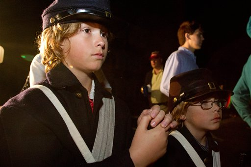 William McCaskill, 10, left, and his brother Alex McCaskill, 7,of Lugoff, SC, gather at White Point Garden near Fort Sumter Tuesday, April 12, 2011 for a candlelight sunrise concert to commemorate the moment the first shots of the Civil War were fired in Charleston, S.C. The South Carolina ceremony Tuesday begins the four-year national commemoration of the 150th anniversary of the Civil War.