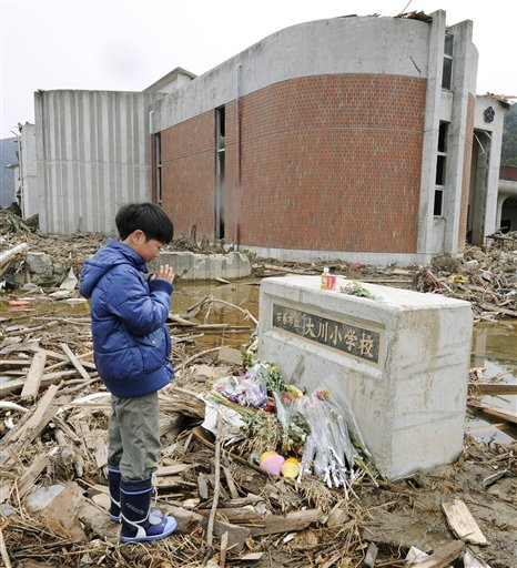 A Japanese student prays for victims at an elementary school in Ishinomaki, northeastern Japan, on Monday April 11, 2011. Exactly a month ago a massive earthquake and tsunami ravaged Japan's northeastern coastal region.