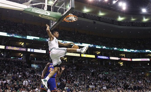 Boston Celtics guard Avery Bradley, top, follows through on a slam dunk after beating New York Knicks guard Anthony Carter on a fast break during the first quarter Wednesday in Boston.