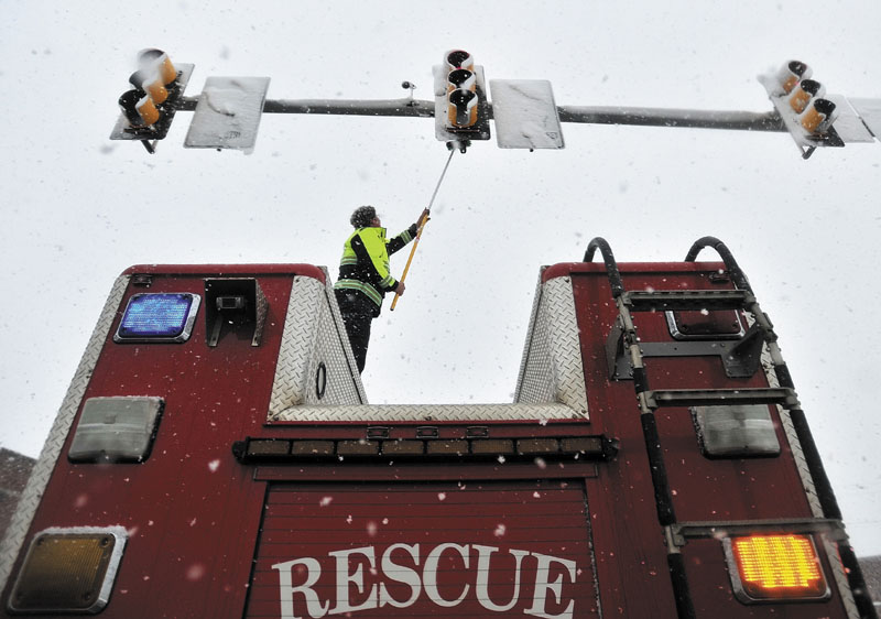Waterville Fire Department Lt. Scott Holst clears the traffic light sensors free from snow Friday at the Post Office Square intersection in Waterville on Friday. Heavy snow wreaked havoc during the morning Friday, covering the sensors and setting lights on an unyielding red.