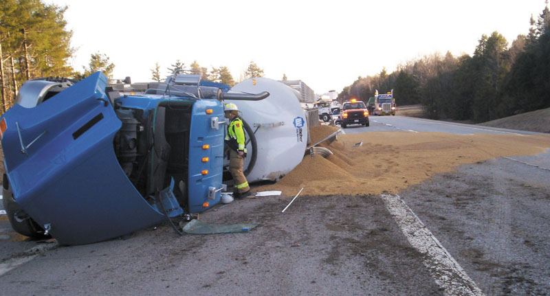 Emergency crews work Friday to right an 18-wheeler that rolled over at 6:40 a.m., blocking the southbound lanes of Interstate 95. The truck's driver, Nelson Plourde, 51, of Gardiner, was taken to MaineGeneral Medical Center in Augusta with a severe cut on an elbow. The truck had just loaded grain at Blue Seal Feeds on Riverside Drive.