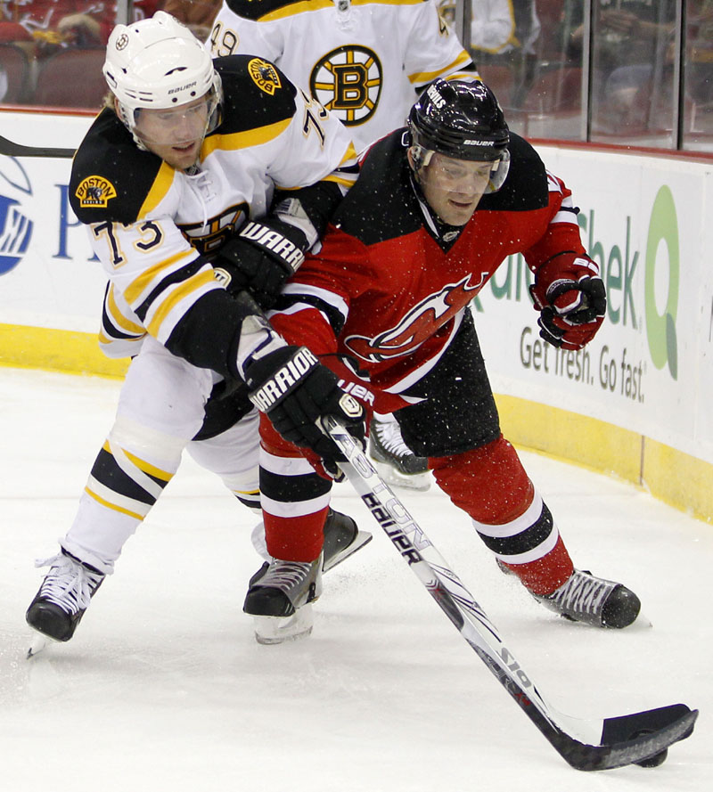 GIVING CHASE: Boston Bruins right wing Michael Ryder, left, and New Jersey Devils defenseman Andy Greene compete for the puck in the first period Sunday in Newark, N.J. The Bruins lost the regular-season finale, 3-2.