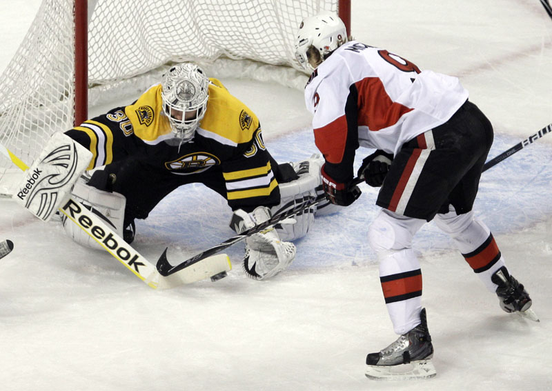 Puck stops here: Boston Bruins goalie Tim Thomas, left, makes a stick save as Ottawa's Milan Mihalek looks for a rebound during the first period of their game Saturday in Boston. Thomas had 31 saves to help the Bruins win 3-1.