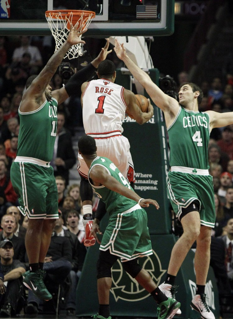 SLICING UP THE DEFENSE: Chicago Bulls guard Derrick Rose, center, drives to the basket against Boston Celtics defenders Glen Davis, left, Rajon Rondo, bottom, and Nenad Krstic during the first quarter Thursday night in Chicago. Rose scored a game-high 30 points as the Bulls won 97-81 and moved closer to clinching the No. 1 seed in the Eastern Conference.