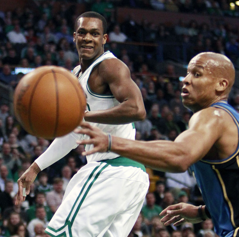 PASSING FANCY: Boston Celtics point guard Rajon Rondo, left, passes into the post while Washington Wizards guard Maurice Evans looks on in the first quarter Friday night in Boston. Rajon Rondo had 20 points and 14 assists to lead the Celtics to a 104-88 victory.