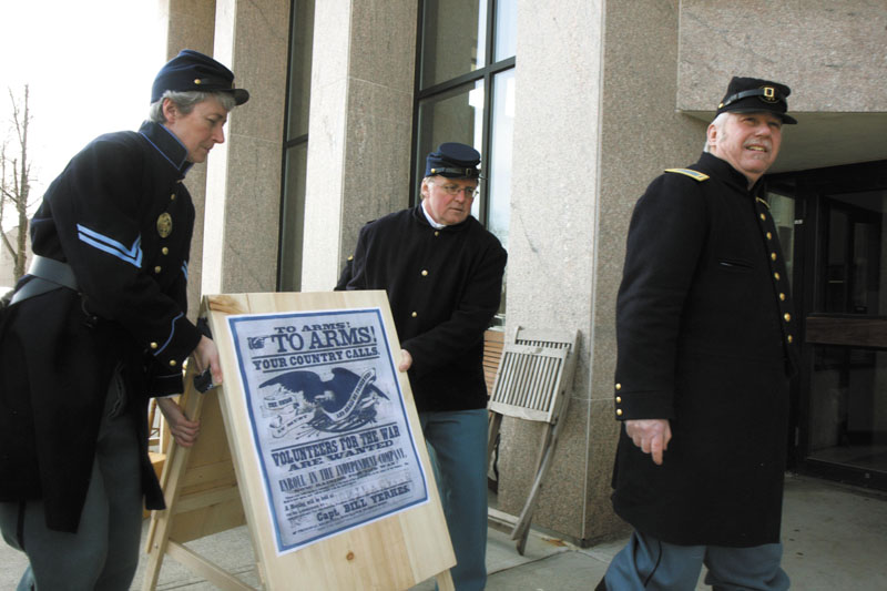 "Darlene Coltart, left, and David Wylie, of Company B, 20th Maine Regiment, work together to place a sign outside the Maine State Museum during a ""recruiting drive"" re-enactment on Saturday in Augusta to commemorate the start of the Civil War. Far right is Paul Dudley, president of Company B, 20th Maine Regiment."