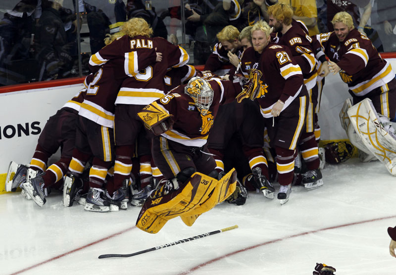 1ST-TIME CHAMPIONS: Minnesota Duluth goalie Kenny Reiter, center, leaps in the air as his teammates celebrate in the background after beating Michigan 3-2 in overtime in the championship game Saturday night in St. Paul, Minn. It's the first championship in Minnesota Duluth's history.