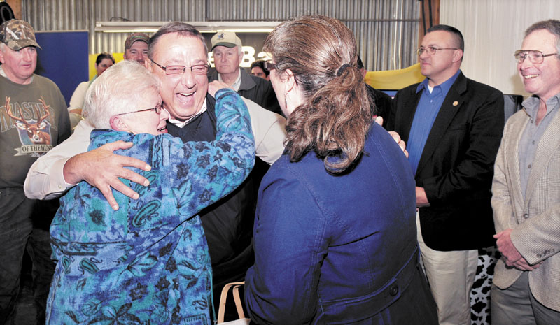 """Gov. Paul LePage gets a hug from Ursala LePage, no relation, of Knox, as Mary Anne Kinney gave him a basket of maple products during the 51st annual open house at Ingraham Equipment in Knox on Wednesday. LePage spoke with area farmers and said the state will become pro business and not an adversary to growth that has made farming an """"endangered species."""" LePage further cited the newspaper industry as struggling and said,"""" I""""m doing my part to sell papers."""" At right is Commissioner of Agriculture Walter Whitcomb."""