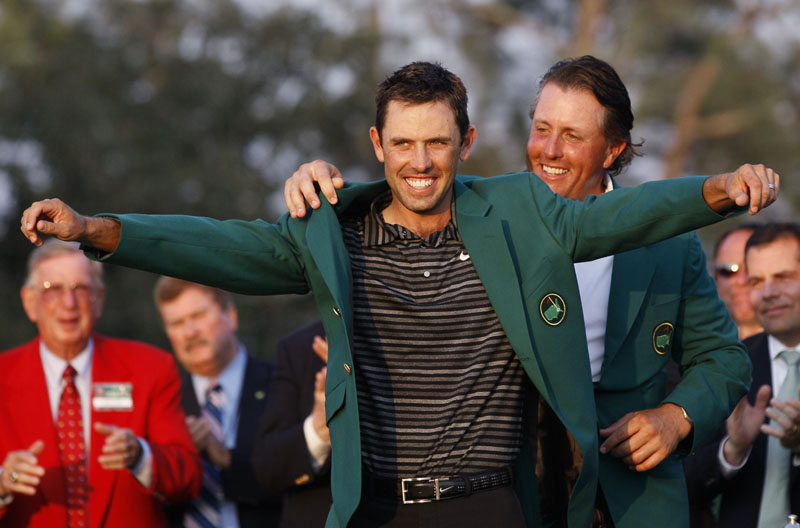 NEW WINNER: Former Masters champ Phil Mickelson, back, helps Charl Schwartzel put on his green jacket after winning the Masters on Sunday evening in Augusta, Ga.