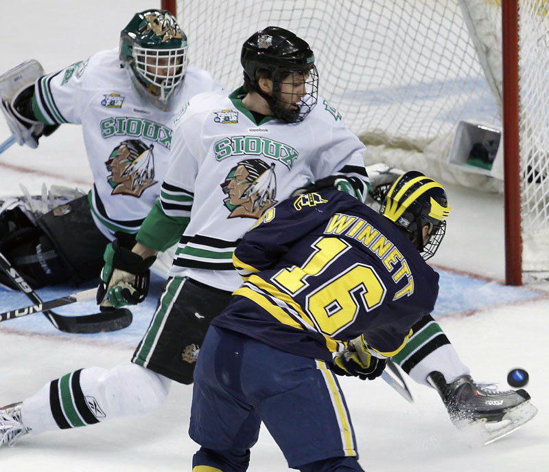 GETTING THROUGH: Michigan left wing Ben Winnett, right, shoots the puck under the skate of North Dakota defenseman Derek Forbort, center, to score on North Dakota goalie Aaron Dell during the first period of a Frozen Four semifinal Thursday night in St. Paul, Minn. That goal proved to be the game-winner as Michigan upset North Dakota 2-0 to reach Saturday night's championship game against Minnesota-Duluth.