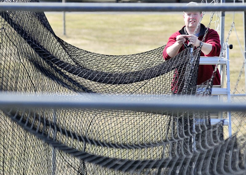 GETTING READY: Greg Stewart hangs up a batting cage net Saturday morning at Morton Field in Augusta. Stewart and other volunteers were working around the complex shoveling snow from in front buildings and getting the fields ready. Most of the complex was snow-free but some piles lingered in shady spots.