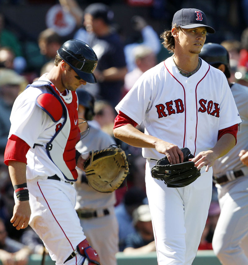 TOUGH TO WATCH: Boston Red Sox pitcher Clay Buchholz, right, and catcher Jarrod Saltalamacchia look away after Buchholz gives up a three-run home run to New York Yankees catcher Russell Martin during the fourth inning Saturday at Fenway Park in Boston. Buchholz allowed five runs in 3 2/3 innings during a 9-4 loss as the Red Sox fell to 1-7.