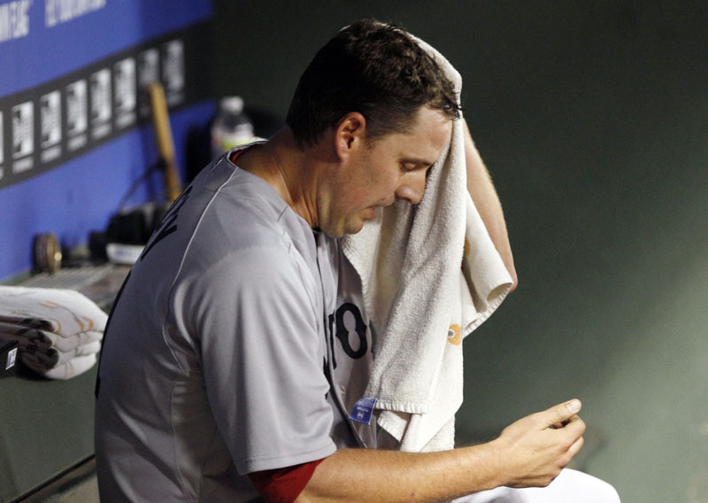 QUICK HOOK: Boston Red Sox pitcher John Lackey sits in the dugout after he was pulled from the game in the fourth inning against the Texas Rangers on Saturday night Arlington, Texas. Lackey gave up nine runs and 10 hits in 3 2/3 innings. Boston lost 12-5.