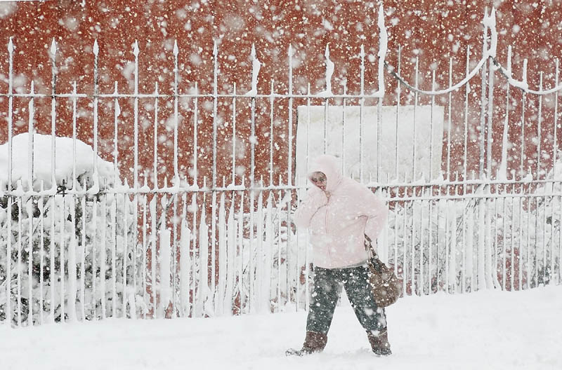 A bundled-up pedestrian walks along a snowy Water Street during the April Fools' Day snowstorm on Friday in downtown Augusta.