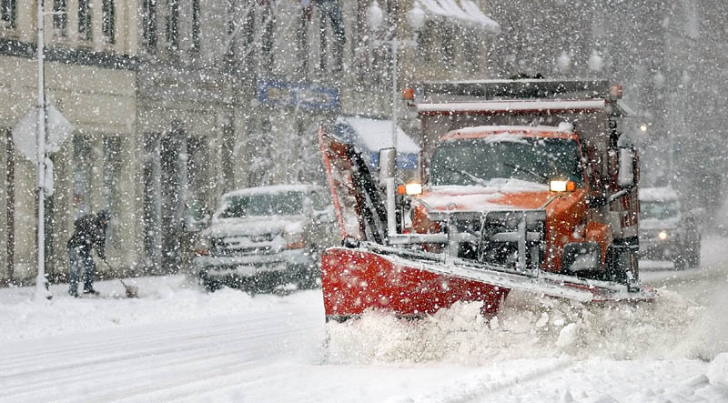 CLEANING UP: A snow shoveler, left, and a City of Augusta plow truck both do their parts to clear snow on Water Street this afternoon in downtown Augusta.