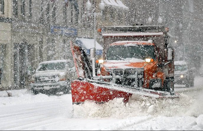 A snow shoveler, left, and a city of Augusta plow truck both do their parts to clear snow on Water Street during the April Fools' Day snowstorm on Friday in downtown Augusta.