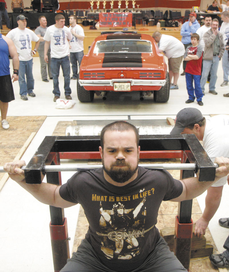 Photo by Jeff Pouland A CAR LIFT: Paul Sousa of Weymouth, Mass. practices his technique for the car squat event before it officially gets underway at the fifth annual Central Maine Strongman competition Saturday at the Augusta Armory.
