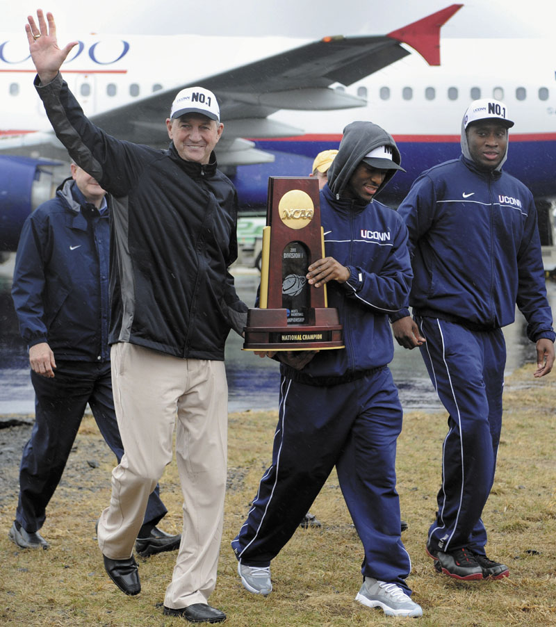 LOOK OF A CHAMP: Connecticut head coach Jim Calhoun, left, and senior Kemba Walker carry the championship trophy as they arrive for a rally Tuesday at Bradley International Airport in Windsor Locks, Conn.