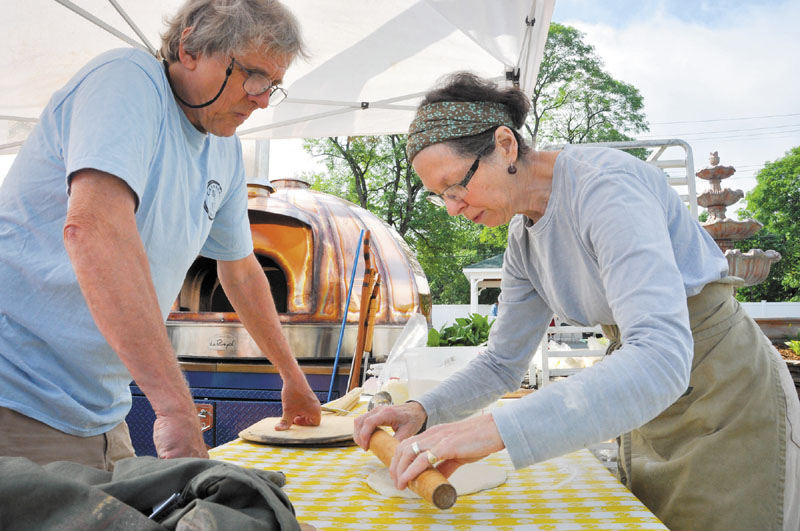 ALSO COOKING: Mark Roman and MaryAnn Reynolds, both of Solon, prepare some pizza dough for the wood-fired baking oven shown in the background at Saturday's Artisan Bread Fair in Skowhegan.
