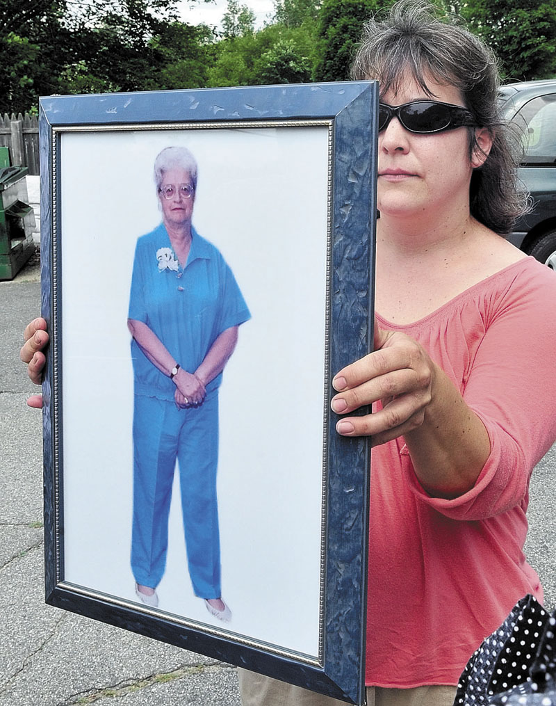 FAMILY: Sheila Butterfield holds a portrait of her relative Grace Burton during a press conference with family members and police on Tuesday at the apartment where Burton was recently killed in Farmington.