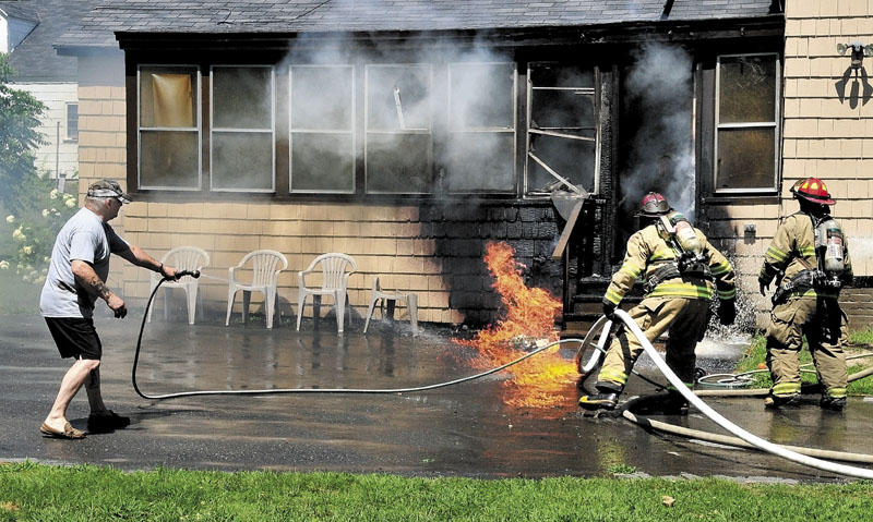 NEIGHBORLY HELP: Neighbor Rick Burgess Sr. uses his garden hose along with Waterville firefighters to douse flames at a residence on May Street in Waterville on Saturday. Deborah Kilsby and Randy LaPointe also helped rescue a dog from the home.