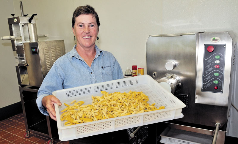 FRESH: Standing in front of pasta- and ravioli-making equipment, Mary Burr holds a tray of penne she and her husband, Bob, made at their Pasta Fresca business at Blue Ribbon Farm in Mercer. The couple will use local grains that will be milled at the grist mill in Skowhegan to make their pasta.