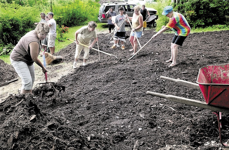 SLOWING EROSION: In an effort to slow erosion and reduce algae blooms, homeowners, campers and members of the Youth Conservation Corp. spread mulch on a hillside at the Wood Haven trust cottage on Pattee Pond in Winslow. Owners and sisters from left are Whendy Smith, Linda Daigle, Kim MacKay and Carolyn Albert.