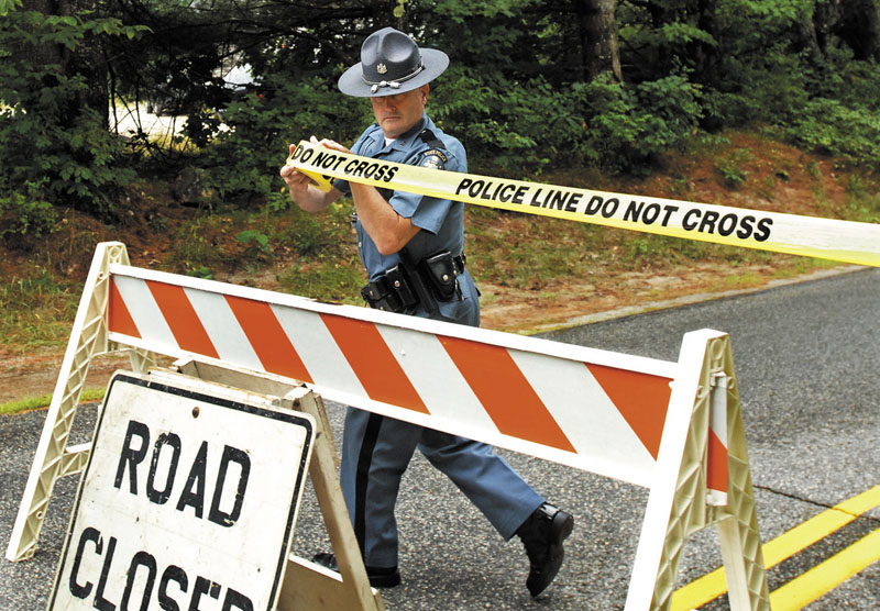 CLOSED: Maine State Police Trooper Steven Green seals off part of Bennett Road in New Gloucester on Tuesday while investigators collected evidence after a fatal shooting on Monday night.