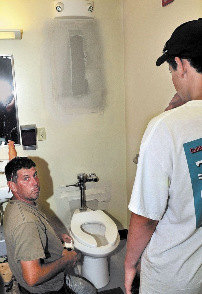 BREAK AND ENTRY: Richard Prentiss, left, and his son Ryan repair two holes in a bathroom wall on Tuesday after thieves broke into Rafting Randy's Whitewater Supply business in downtown Skowhegan earlier. The thieves broke a gate and sawed through two doors to gain entry and stole $3,000 worth of merchandise and cash.