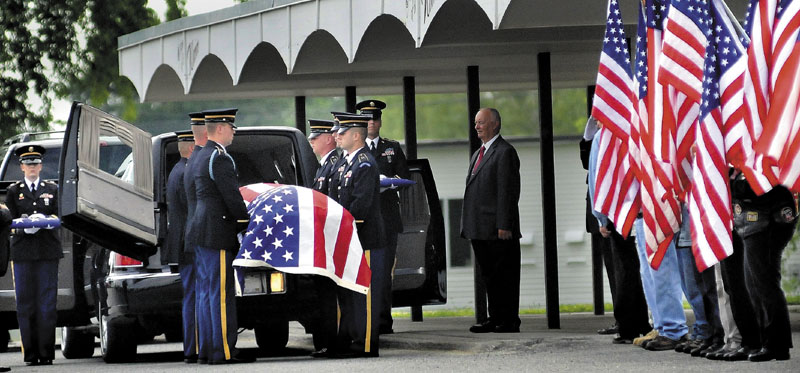 RETURN JOURNEY: Members of the Maine Army National Guard on Friday carry the casket of Pfc. Tyler M. Springmann, 19, of Hartland, who was killed in Afghanistan on July 17. Springmann's funeral was in the gymnasium at Nokomis Regional High School in Newport — the same place where he graduated last year.