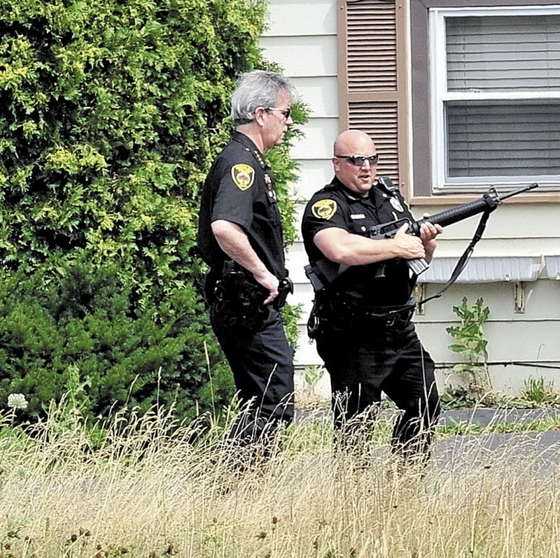 STANDOFF: Winslow Police Chief Jeffrey Fenlason, left, and officer Joshua Veilleux and other police search for a man in Benton on Monday. As of Monday evening, the man had not been found.