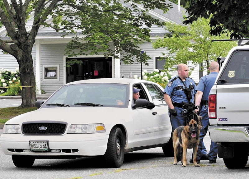 ROBBERY: State police troopers speak with Waldo County Sheriff Scott Story outside the Down East Credit Union on School Street in Unity after it was robbed on Friday afternoon. Police with tracking dogs searched neighborhoods and the woods for the robber.